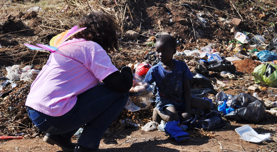 One of our fairies talking to a child playing amongst trash in his neighborhood